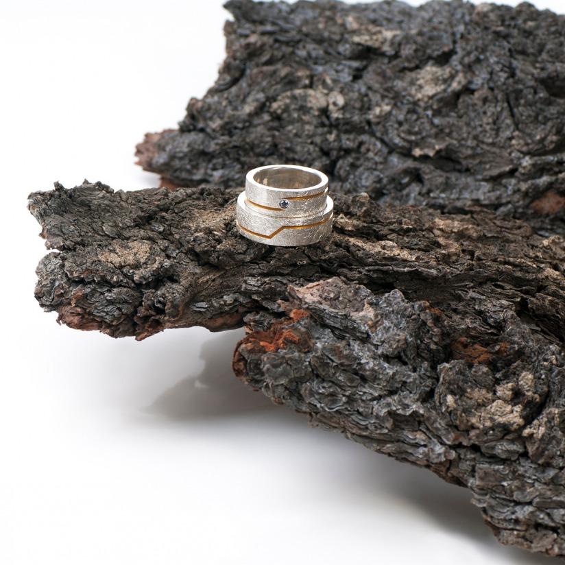 Ein vergoldetes vertieftes Band wechselt die Position auf diesen silbernen Ringen von Edel und Stein Esslingen